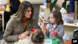 FILE - First lady Melania Trump watches as children form objects from Play-Doh at Joint Base Elmendorf-Richardson, Alaska, Nov. 10, 2017.