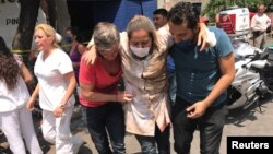 19일 멕시코시티에 규모 7.1 규모의 강진이 발생한 후 부상자를 부축하고 있다.