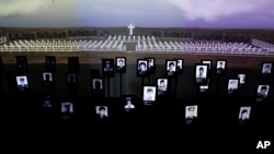 FILE - Photographs of Argentine soldiers who died in the Falklands War between Argentina and Great Britain are displayed inside Malvinas Museum in Buenos Aires, Argentina, Sept. 18, 2015. The two countries reached a deal, Dec. 20, 2016, to identify the remains of over 100 Argentine soldiers buried in the Falkland Islands after the 1982 war.