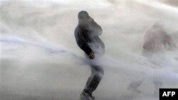 """Бельгийская полиция обстреливает демонстрантов из """"водяной пушки""""."""