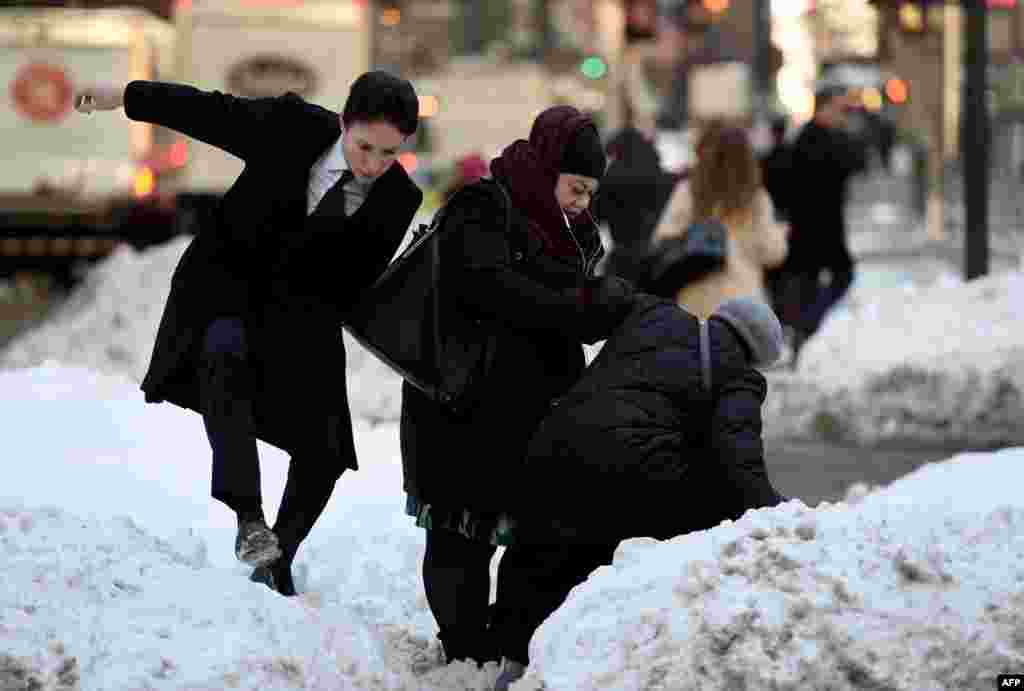 People try to navigate a snowbank in the middle of Park Avenue as New Yorkers return to work after the city was hit with a record-setting snowfall.