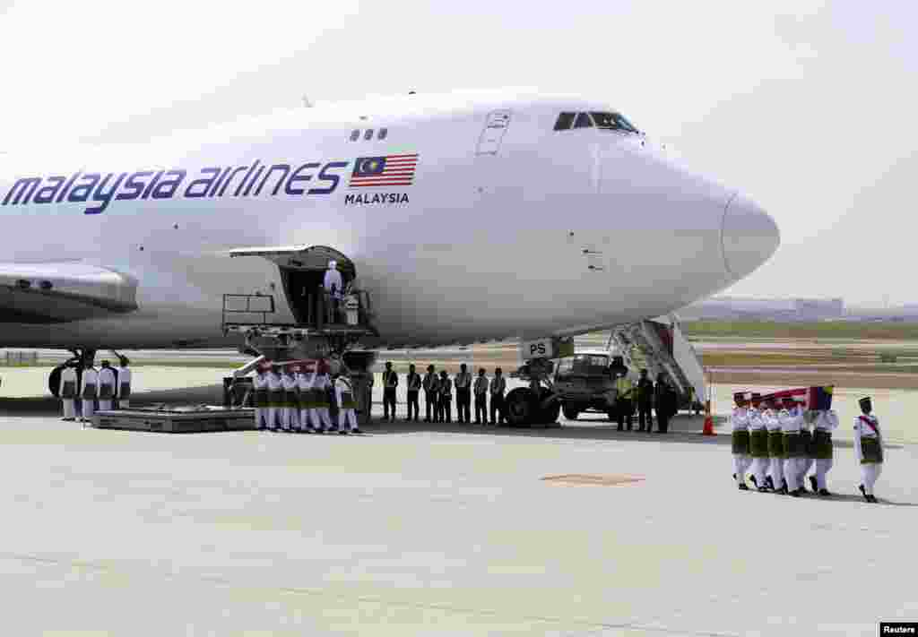 The remains of the passengers of downed Malaysia Airlines MH17 are carried from the transport plane during a repatriation ceremony, in Sepang, Aug. 22, 2014.