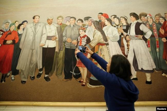 中国全国人大会议期间的一个小组讨论会会场,有记者拍摄一幅描绘毛泽东主席会见各民族群众的画。(2018年3月8日))