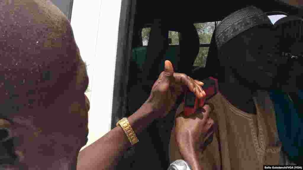 Mr. Jibrin Zakari jami'in kiwon lafiya daga Najeriya na auna zafin jikin fasenjoji dake shiga Najeriya, domin tantance ko suna dauke da cutar Ebola.