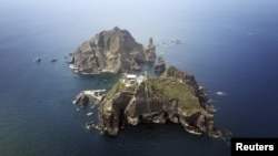 FILE - A set of remote islands, called Dokdo in Korean and Takeshima in Japanese, as seen from a helicopter.