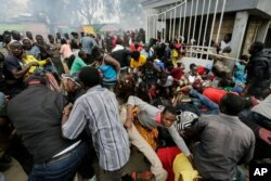 FILE - Residents desperate for a planned distribution of food for those suffering under Kenya's coronavirus-related movement restrictions push through a gate and create a stampede, at a district office in the Kibera slum of Nairobi.