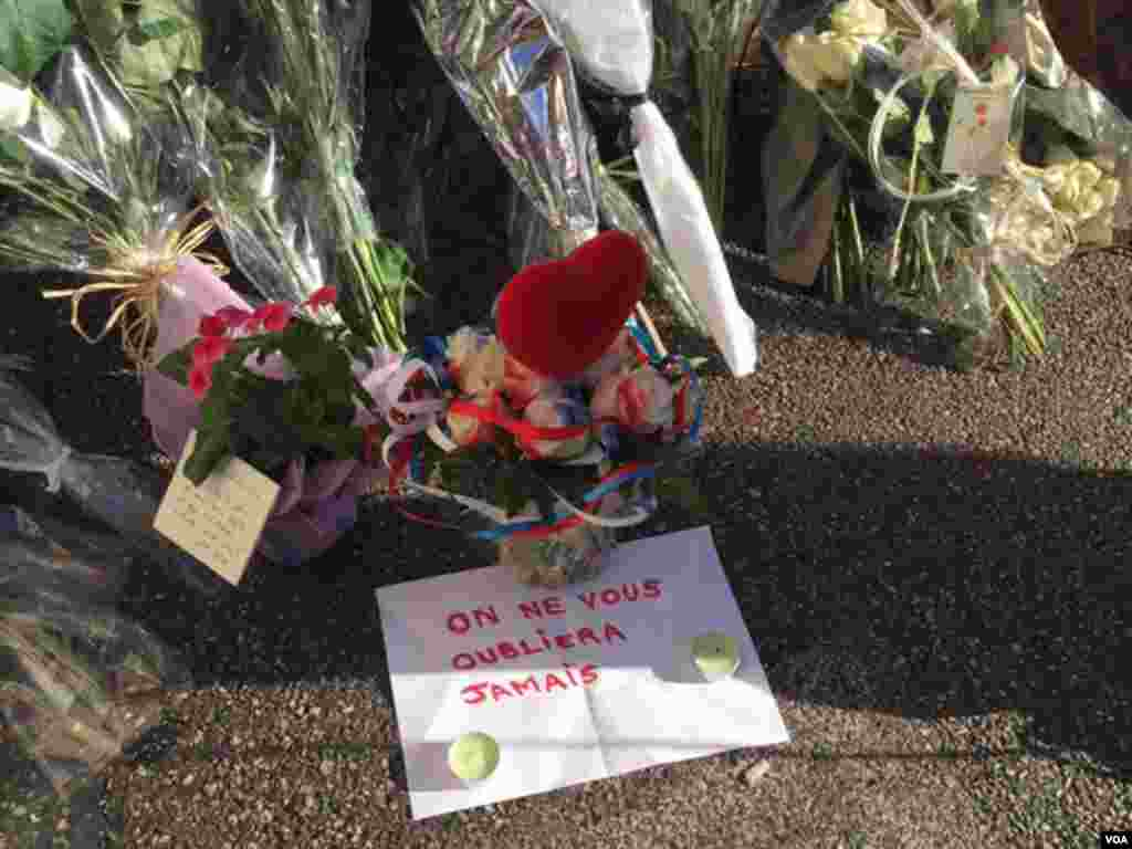 "Sign next to flowers left to honor Bastille Day attack victims says ""We Will Never Forget"" in Nice, France, July 2016. (Photo: VOA Persian Service)"