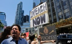 FILE - Protesters rally outside a Trump hotel to call for the impeachment of President Donald Trump, July 2, 2017, in New York.
