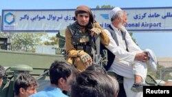 កងកម្លាំងតាលីបង់អង្គុយលើយានយន្តមួយនៅខាងក្រៅអាកាសយានដ្ឋានអន្តរជាតិ Hamid Karzai របស់ក្រុងកាប៊ុលកាលពីថ្ងៃទី១៦ ខែសីហា ឆ្នាំ២០២១។