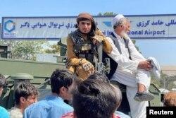 Seorang anggota pasukan Taliban (kiri) duduk di atas kendaraan lapis baja di luar Bandara Internasional Hamid Karzai di Kabul, Afghanistan, 16 Agustus 2021. (REUTERS/Stringer)