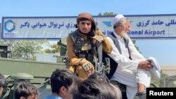 Seorang anggota pasukan Taliban (kiri) duduk di atas kendaraan lapis baja di luar Bandara Internasional Hamid Karzai di Kabul, Afghanistan 16 Agustus 2021. (Foto: Reuters)