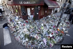 "FILE - People mourn outside ""Le Carillon"" restaurant a week after a series of deadly attacks in Paris, Nov. 22, 2015."
