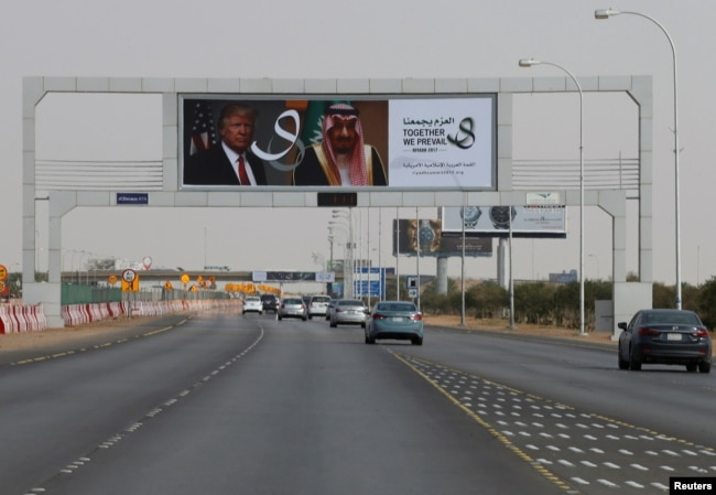 U.S. President Donald Trump's and Saudi Arabia's King's Salman bin Abdulaziz Al Saud's photos are seen with flags of both countries on airport road as part of celebrations to welcome United States President Donald Trump, in Riyadh, Saudi Arabia, May 19, 2