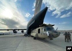 ក្នុងរូបថតផ្តល់ឱ្យដោយក្រសួងការពារជាតិអាមេរិកនេះ យន្តហោះប្រភេទ CH-47 Chinook ត្រូវបានដឹកចូលកន្ទុយយន្តហោះធំយោធាប្រភេទ C-17 Globemaster របស់កងទ័ពអាកាសអាមេរិក នៅអាកាសយានដ្ឋានក្រុងកាប៊ុលកាលពីថ្ងៃទី២៨ ខែសីហា ឆ្នាំ២០២១។