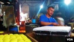 Seorang perajin tahu di Sentra Produksi Tahu Cibuntu, Bandung sedang menyelesaikan produksi tahu. Perajin tahu tempe mengeluhkan kenaikan harga kedelai impor dari Amerika (foto: VOA/Wulan).