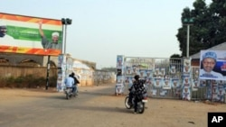 Members of the Party Loyalists drive their motocycles outside the entrance of a park in front of posters featuring Nigeria's opposition leader Mohammadu Buhari (R) and Nigeria's President Goodluck Jonathan and his Vice President Namadi Sambo (L) in Kad