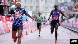 Shura Kitata, à gauche, traverse la ligne d'arrivée devant Vincent Kipchumba et Sisay Lemma au marathon de Londres, Angleterre, le 4 octobre 2020.
