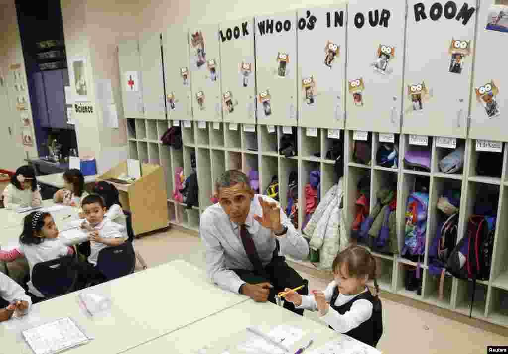 Tổng thống Barack Obama ngồi chơi với em Emily Hare khi ông đến thăm những em học sinh 3-4 tuổi trong một lớp mầm non tại trường tiểu Học Powell ở thủ đô Washington, Mỹ.