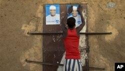 Seorang pemuda Mali menempelkan poster salah satu kandidat presiden dalam pemilihan presiden Mali di Gao, Mali (25/7)
