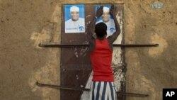 28일 아프리카 말리에서 대선이 열리는 가운데 한 남성이 한 후보의 유세 포스터를 벽에 붙이고 있다.