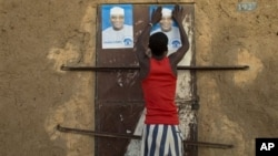 Young man glues campaign posters for Ibrahim Boubacar Keita on top of a pair posters for rival Dramane Dembele, Gao, Mali, July 25, 2013.