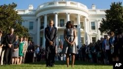 Oq uy oldida Prezident Barak Obama va uning rafiqasi Mishel Obama boshqa ma'muriyat xodimlari bilan 11-sentabr xurujlarida qurbon bo'lganlarni xotirlab bir daqiqalik sukut saqlamoqda, 11-sentabr, 2015-yil.
