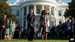 President Barack Obama, first lady Michelle Obama, and others, pause on the South Lawn of the White House in Washington, Sept. 11, 2015, as they observe a moment of silence to mark the 14th anniversary of the 9/11 attacks.