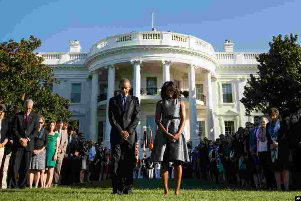 President Barack Obama, first lady Michelle Obama and others observe a moment of silence to mark the 14th anniversary of the 9/11 attacks, on the South Lawn of the White House in Washington, Sept. 11, 2015.