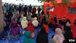 Pejabat pemerintah setempat, IOM dan UNHCR memberikan pengarahan kepada pengungsi Rohingya yang tiba di Kabupaten Aceh Timur, Sabtu, 5 Juni 2021. (VOA/Anugrah)