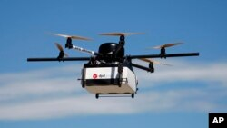 FILE - GeoPost, a package delivery subsidiary of LaPoste, tested this prototype drone carrying a parcel in Pourrieres, southern France, June 23, 2015.