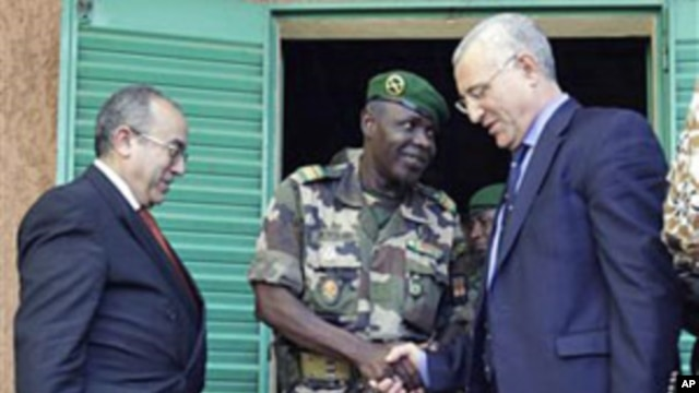 Salou Djibo (C), leader of the military junta that overthrew Niger's strongman president days earlier, shakes hands with the U.N's Said Djinnit as Ramtane Lamamra of the African Union looks on, following talks between the junta and international envoys at