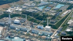 FILE - An aerial view shows the tsunami-crippled Fukushima Daiichi nuclear power plant and its contaminated water storage tanks.