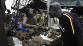 A man buys bush meat at a market in Yopougon, Abidjan, May 27, 2006.