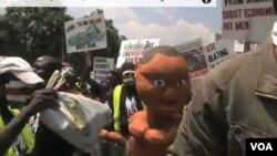 抗議者舉著巨大的泡沫塑料做的嬰兒雕塑,抗議他們所說的置兒童於不顧的領導人。