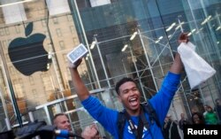 One of the first customers to purchase the Apple iPhone 5S celebrates after exiting the Apple Retail Store on Fifth Avenue in Manhattan, New York, Sept. 20, 2013.