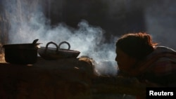 A woman uses firewood to cook food in her home, in Sapay, Nepal, about 900 kilometers from Kathmandu, Feb. 17, 2014.