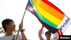 Participants hold a rainbow flag while attending Vietnam's first-ever gay pride parade, Hanoi, Aug. 5, 2012.