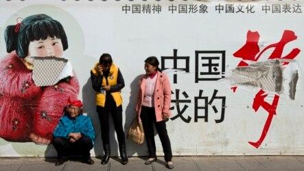 """2014年3月2日昆明火车站外""""中国梦""""宣传海报下的乘客"""