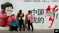 """Passengers wait in front of a broken propaganda poster featuring """"the China Dream"""" outside the Kunming Railway Station in Kunming, in western China's Yunnan province, March 2, 2014."""