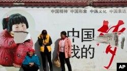 """2014年3月2号中国西南城市昆明火车站被歹徒砍破的""""中国梦""""的宣传画下的群众"""