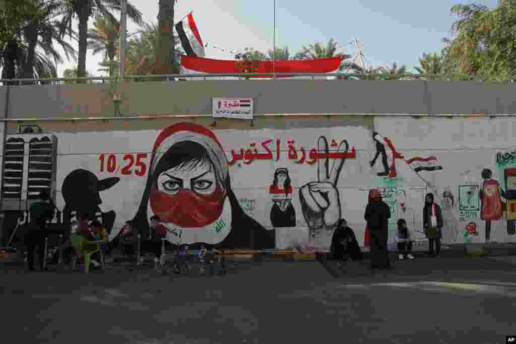 تجمع معترضان عراقی در کنار یک نقاشی دیواری با عنوان انقلاب اکتبر