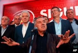 FILE - Milo Djukanovic, center, then the prime minister of Montenegro, speaks in his headquarters in Podgorica, Oct. 17, 2016. Since then, a Montenegrin court has confirmed indictments against 14 people for allegedly masterminding a coup attempt in Montenegro that included an attempt on Djukanovic's life.