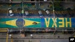 """Uma estrada do Rio de Janeiro tem escrito """"Hexa Brasil"""", pois os brasileiros esperam alcançar a sexta taça do Mundial de Futebol"""