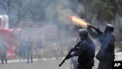 Polisi Brazil menembakkan peluru karet ke arah demonstran di kota Brasilia (15/6). Para pejabat kota di Brazil membatalkan rencana menaikkan tarip transportasi umum yang memicu demonstrasi anti pemerintah.