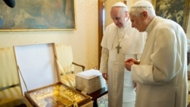 Pope Francis (L) exchanges a gift with Pope Emeritus Benedict XVI at the Castel Gandolfo summer residence, south of Rome, March 23, 2013.