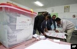 Des responsables électoraux recueillant des suffrages après le vote du 23 octobre