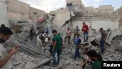 ພວກຜູ້ຊາຍ ພາກັນຊອກຫາ ພວກລອດຊີວິດ ທີ່ຕິດຢູ່ພາຍ ໃຕ້ກອງຊາກຫັກພັງຂອງອາຄານຫຼັງຈາກໄດ້ຮັບຄວາມເສຍ ຫາຍ ຈາກການໂຈມຕີ ທາງອາກາດ ໃສ່ບໍລິເວນ Kadi Askar ຂອງເມືອງ Aleppo ບ່ອນທີ່ພວກກະບົດ ໄດ້ຍຶດເອົາໃນຊີເຣຍ, ວັນທີ 8 ກໍລະກົດ 2016.