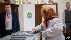 Seorang perempuan Moldova memberikan suara dalam pilpres di sebuah TPS di kota Chisinau hari Minggu (30/10).