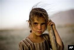Une fillette afghane répare des nids-de-poule sur la route entre Kaboul et Bagram en comptant sur la générosité des automobilistes