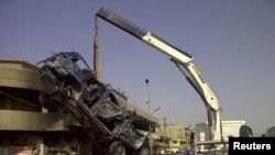 Một chiếc xe bị cháy được đưa ra khỏi hiện trường sau vụ đánh bom nhắm vào các tín đồ Hồi giáo Shia ở Baghdad, ngày 13/6/2012